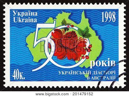 UKRAINE - CIRCA 1998: A stamp printed in Ukraine issued for the 50th anniversary of Ukrainians in Australia shows map of Australia and Waratah, circa 1998.