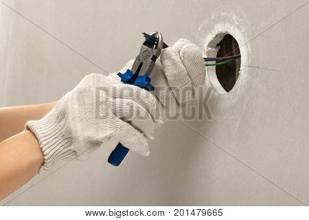 hand of electrician cutting wires with clippers during repair