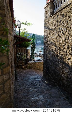 ULCINJ, MONTENEGRO - AUGUST 1, 2017: Old narrow street in Stari Grad of Ulcinj, Montenegro. The fortress in the Old town in a sunny summer day.