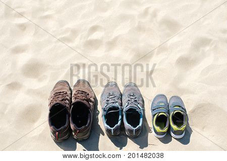 Running shoes family, the top view of the sand, vacation and holidays.
