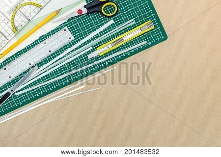 Yellow Utility Knife With Scissors, Ruler, Pencil And Cutting Mat On Kraft Paper Background