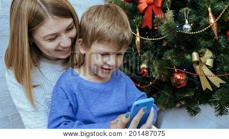 Young happy mother and son with mobile phone are sitting together near decorated christmas tree. Happy family at xmas celebrates.