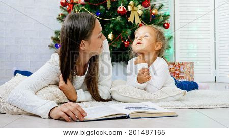Happy family mother and cute little daughter lying on the floor and reading book with christmas tree on the background at xmas eve.