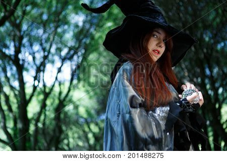 Portrait of young witch with long hair with magic ball in hands, long black hat in gloomy forest