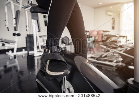 Young asian woman exercising on the xtrainer machines in gym