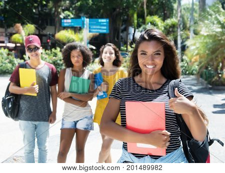 Laughing latin american female student showing thumb with group of international students outdoor in the city in the summer