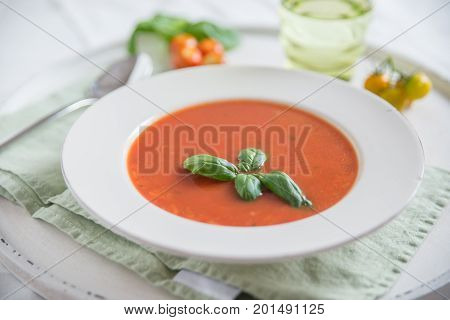 Tomato soup with basil leaves in a bowl