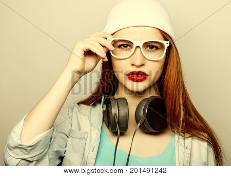 Young redhair woman with headphones listening music.