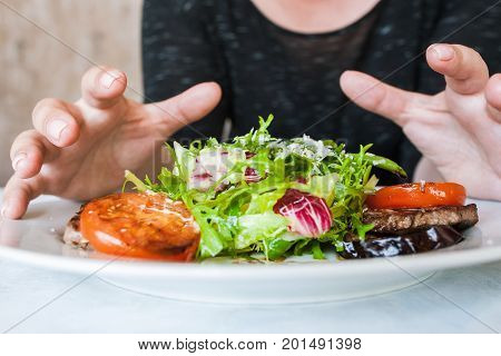 Woman attacks medallions with salad, hunger and impatience concept. Grilled meat, tomatoes, eggplant and green ruccola with grated cheese, close up picture