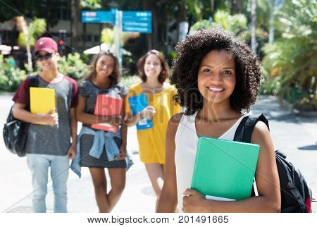 Laughing african american female student with group of international students outdoor in the city in the summer