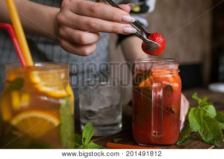 Waiter preparing strawberry cocktail in restaurant. Fresh citrus and berry cold drink with mint and ice on wooden table, concept of refreshment and satisfying thirst, close up picture