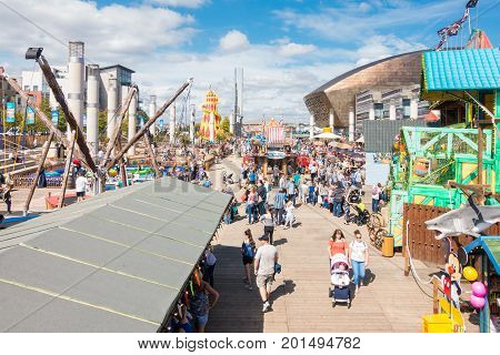 Cardiff United Kingdom - August 26 2017: People enjoying themselves on a sunny day at the Capital FM Cardiff Bay Beach an urban seaside beach fair at Roald Dahl Plass in Cardiff Bay Cardiff.