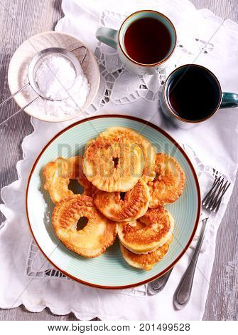 Apple fritters on plate and cups of tea top view