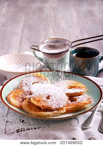 Apple fritters with icing sugar sifting over selective focus