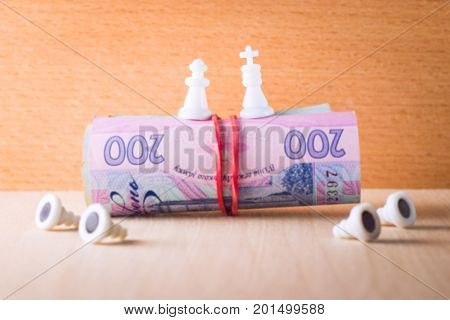 The chess king and the queen stand on a bundle of money at the bottom lay pawns bowing before them
