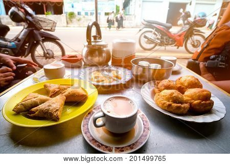 the popular breakfast in Dawei Myanmar is milk tea curry puff samosa roti topped with sweetened condensed milk.