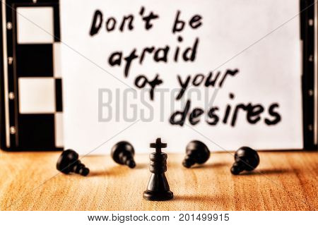 The king and the servants bowing before him against the background of the motivating inscription in English do not be afraid of their desires and the chessboard
