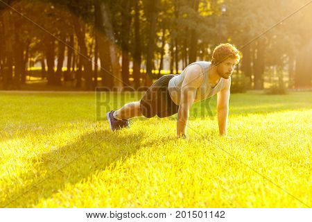 Seriosly bearded redhead athlete concentrate and doing plank. Outdoor
