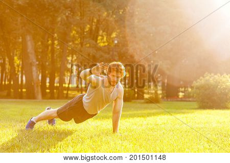 Hello! Training in one summer morning. Young adult bearded man looking in camera and doing exercise. Outdoor