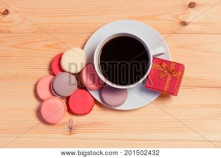 Cup of coffee macaroons and gift box on wooden background