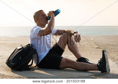Sporty male athlete being thirsty drinking water from fitness shaker bottle and sitting alone on ground with backpack. Resting after training concept