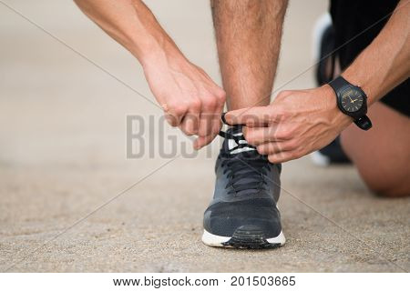 Unrecognizable runner preparing for jogging and lacing shoes. Close-up of man tying lace of running shoe on asphalt. Sport concept