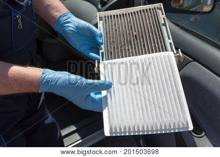 Replacing the pollen air filter. Old and new cabin air filter for the car.