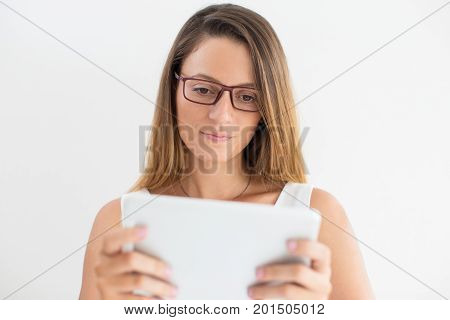Portrait of serious young Caucasian businesswoman or student wearing glasses using touchpad