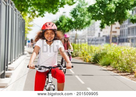 Portrait of happy African girl in safety helmet riding her bicycle on cycle path in summer
