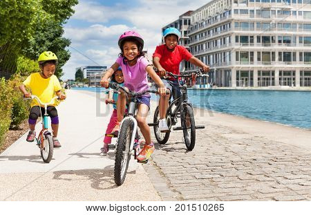 Portrait of African 6-7 years old girl riding bicycle with her friends on a river embankment in summer