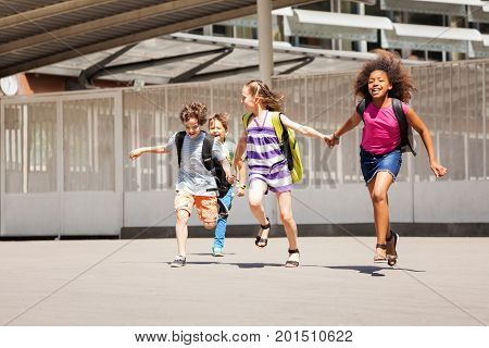 Diverse group of kids running from school happy smiling and holding hands