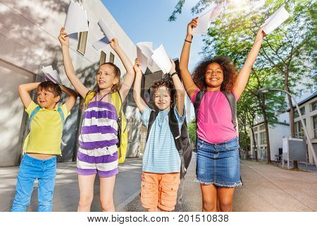 Group of four boys and girls school age with lifted hands stand near the yard