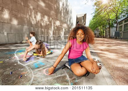 Beautiful curly girl and friends draw hopscotch game on the road