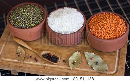 White Rice, Red Lentils And Green Peas Mache On Wooden Tray. Bay Leaves And Black Peppercorns In Woo