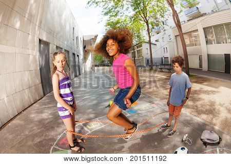 Kids jump over elastic rope smiling and happy with curly African girl in the air poster