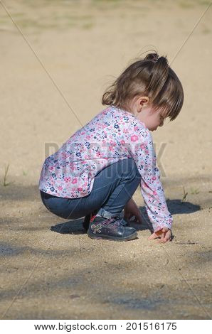 Pretty Little Girl Squatting And Playing In The Ground With The Sand In The Park