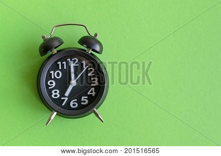 Alarm clock with seven o'clock on green background in minimalistic retro pop art style with place for text. Wake up concept. Back to school. Copy space. Top view.