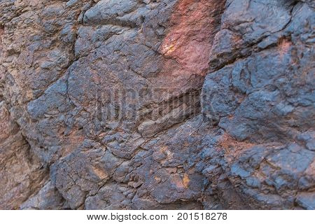 Iron ore texture closeup - natural minerals in the mine. Stone texture of open pit. Extraction of minerals for heavy industry - the texture of the rock containing iron ore and copper