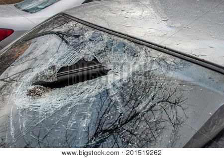 The hole in the broken windshield of the car in the cracks close-up