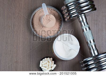 Whey protein in a measuring bucket, amino acids, sports capsules and a metal dumbbell on a wooden background copy space