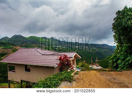 The Road And Houses In The Village On The Slopes Of The Mountains With Clouds. Sabah, Borneo, Malays