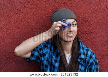hipster girl playing with fidget spinner. Funny portrait of young woman with rotating spinner. Popular trendy stress relieving toy