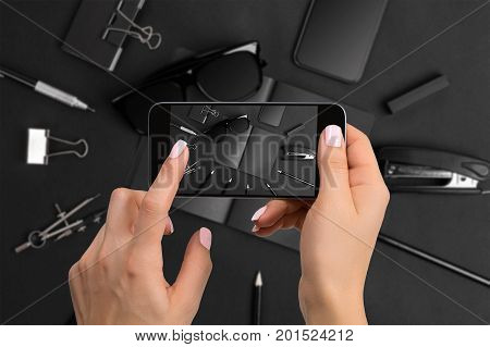 Shooting black stationery on phone's camera. Stationery on black background. Close-up woman's hand holding phone.