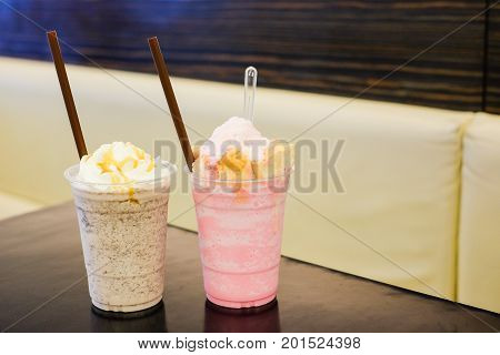Cookie and cream frappe with whipped cream and caramel sauce as well as pink milk shake with soft bread on top for drink background or texture.