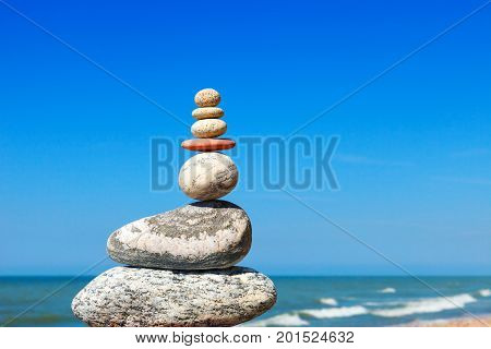 Stones balance on a background of blue sky and sea. Concept of balance and harmony. Rock zen