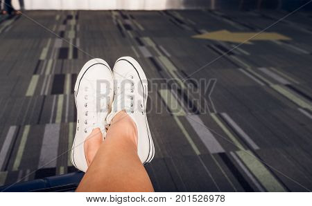 Close up crossed leg wear white sneaker lay on suitcase at airport terminalTravel Vacation concept.