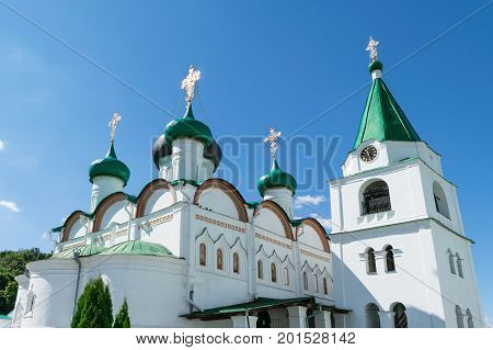 View at Pechersky ascension monastery white clear Sunny day. Is a Church with a bell tower and gold domes. A tumbling bell and a chapel. In the sky floating Cumulus clouds.