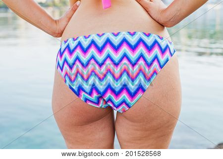 Close up picture of a caucasian young woman's back & butt having cellulite posing in colorful swimwear