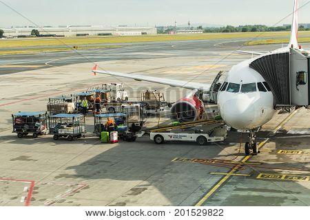 PRAGUE, CZECH REPUBLIC - JUNE 16, 2017: Vaclav Havel Prague International Airport, Ruzyne, Czech Republic. Air plane in airport terminal loading passengers and cargo luggage. Boarding aircraft process.