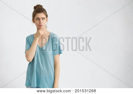 Doubt, Indecisiveness And Dilemma. Studio Shot Of Attractive Thoughtful Girl In Casual Clothes Rubbi